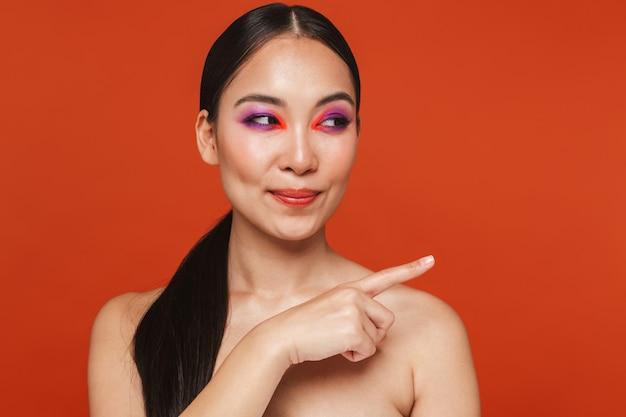 Piękno portret młodej topless azjatyckiej kobiety z brunetką w jasnym makijażu, stojącej odizolowanej na czerwono, wskazującej palcem dalej