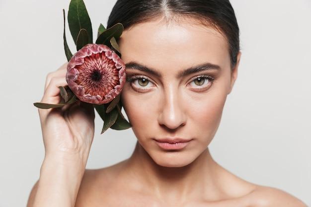 Piękno portret młodej zdrowej atrakcyjnej brunetki kobiety stojącej na białym tle, trzymając kwiat na jej twarzy