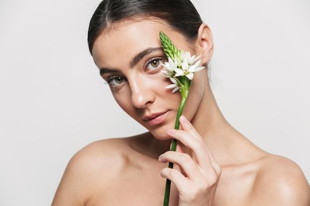 Piękno portret młodej zdrowej atrakcyjnej brunetki kobiety stojącej na białym tle trzymając kwiat roślin w pobliżu jej twarzy