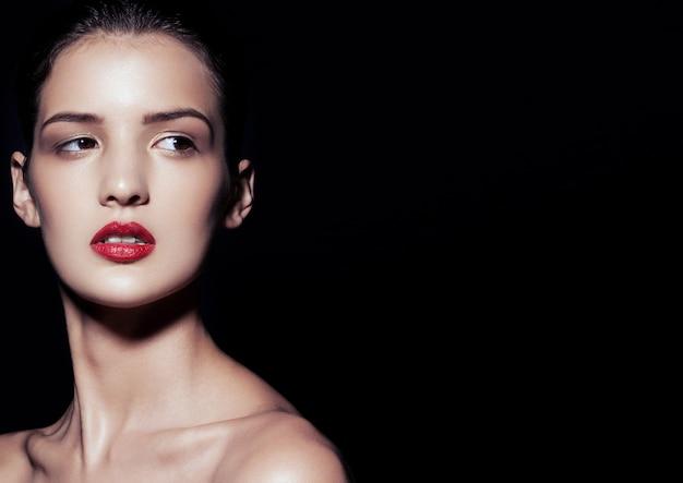 Piękno portret modelu z czerwoną szminką na czarnym tle z miejscem na kopię