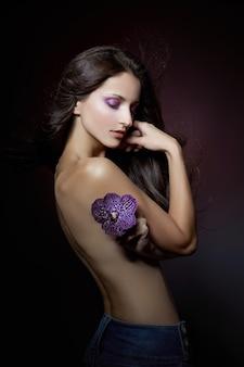 Piękno portret nagiej kobiety z fioletowym kwiatem w dłoniach na ciemnym tle. kosmetyki naturalne, makijaż naturalny