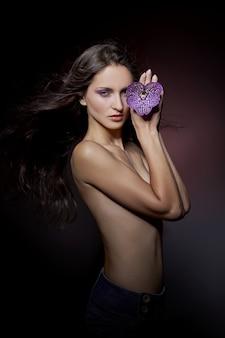 Piękno portret nagiej kobiety z fioletowym kwiatem w dłoniach w ciemności. kosmetyki naturalne, makijaż naturalny