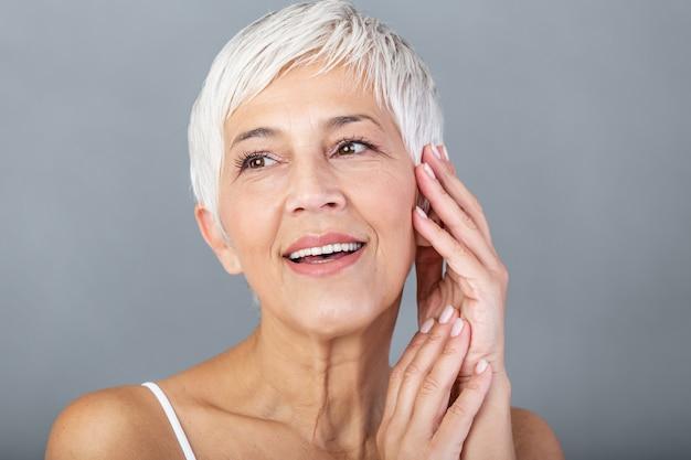 Piękno portret ono uśmiecha się z ręką na twarzy dojrzała kobieta. zbliżenie twarz szczęśliwa starsza kobieta czuje świeżego po anti-aging traktowania. uśmiechnięty piękno patrzeje kamerę z doskonałą skórą.
