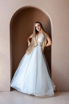 Piękno portret panny młodej w modnej sukni ślubnej z piórami z luksusowym makijażem rozkoszy