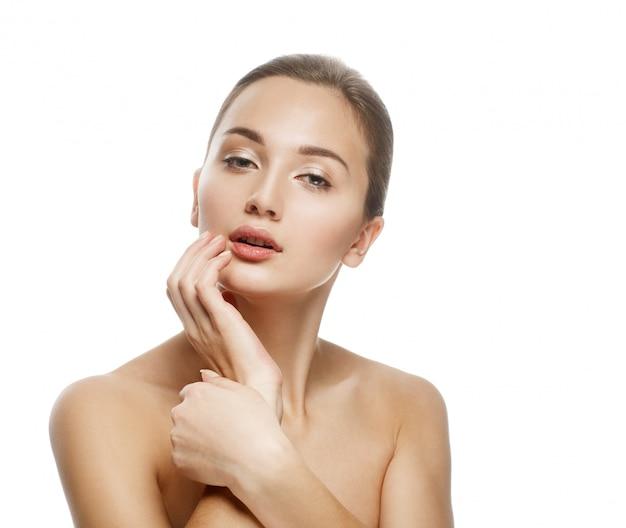 Piękno portret, piękna kobieta dotyka jej twarzy, idealna świeża skóra.