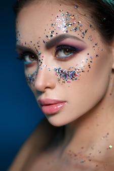 Piękno portret pięknej seksownej dziewczyny z jasnym makijażem i błyszczy w kształcie maski na twarzy