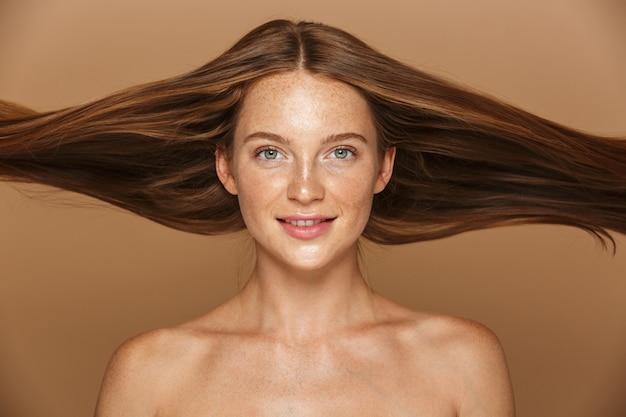 Piękno portret pięknej zdrowej młodej kobiety z długimi rudymi włosami na białym tle nad beżową ścianą