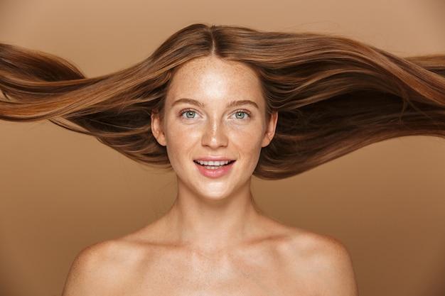 Piękno portret pięknej zdrowej młodej kobiety z długimi rudymi włosami, patrząc na kamery na białym tle nad beżową ścianą