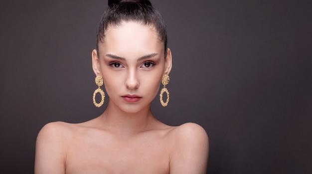 Piękno portret pozuje z złotymi kolczykami kobieta