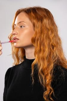 Piękno portret rudowłosej kobiety i błyszczyk na białym makijażu ściennym dla kręconego modelu