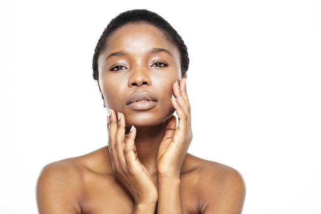Piękno portret ślicznej afroamerykańskiej kobiety patrzącej na kamerę na białym tle
