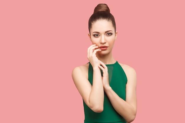Piękno portret spokojny poważne piękna młoda kobieta z kok fryzurę i makijaż w zielonej sukni stojącej, dotykając jej twarzy i patrząc na kamery. kryty strzał studio, na białym tle na różowym tle.