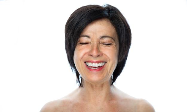 Piękno portret starszej kobiety, śmiejąc się na białym tle