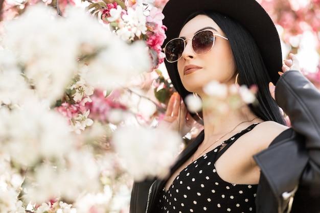 Piękno portret stylowa piękna młoda kobieta w modnych okularach przeciwsłonecznych w eleganckim kapeluszu w modne wiosenne czarne ubrania w parku w pobliżu niesamowitych kwiatów. całkiem wspaniała dziewczyna na spacer w przyrodzie. dobry wypoczynek.