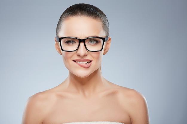 Piękno portret szczęśliwa uśmiechnięta dziewczyna w okularach patrząc na kamery. głowa i ramiona pięknej kobiety przygryzającej dolną wargę. naturalny makijaż, studio, prawdziwe emocje