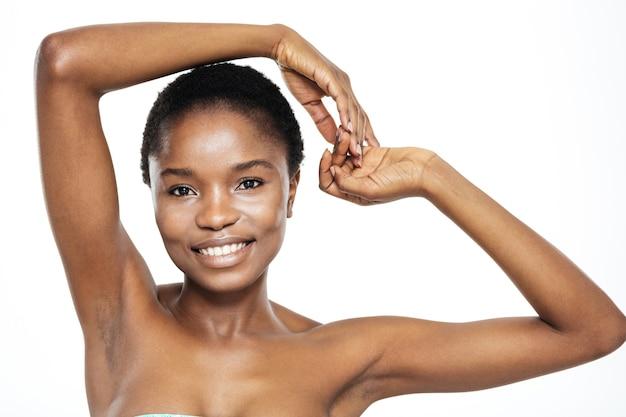 Piękno portret szczęśliwej afroamerykańskiej kobiety patrzącej na kamerę na białym tle