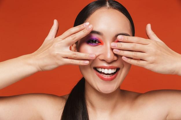 Piękno portret szczęśliwej młodej topless azjatyckiej kobiety z brunetką w jasnym makijażu, stojącej odizolowanej na czerwono