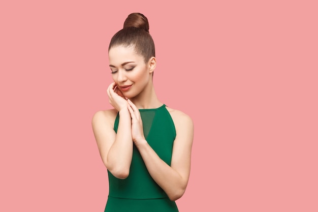 Piękno portret szczęśliwy piękna młoda kobieta z kok fryzurę i makijaż w zielonej sukni stojącej z zamkniętymi oczami, dotykając jej twarzy i uśmiechając się. kryty strzał studio, na białym tle na różowym tle.