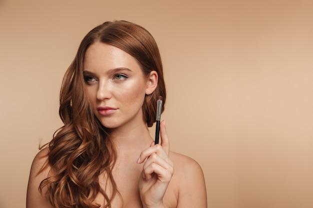 Piękno portret tajemnicza uśmiechnięta imbirowa kobieta patrzeje daleko od z długie włosy podczas gdy trzymający kosmetyki szczotkuje