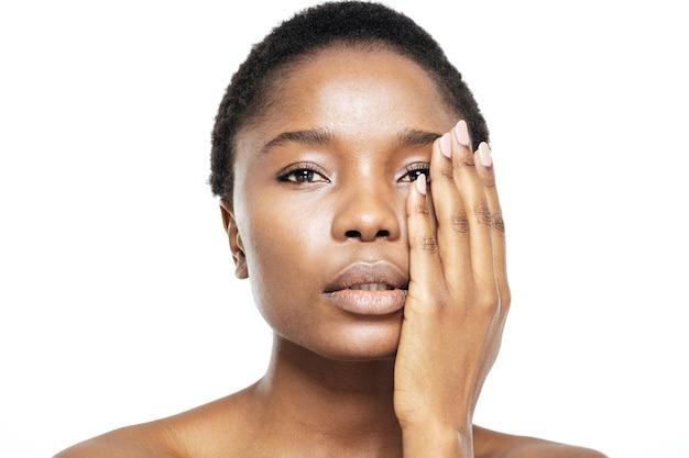 Piękno portret uroczej afroamerykańskiej kobiety dotykającej jej twarzy ręką na białym tle