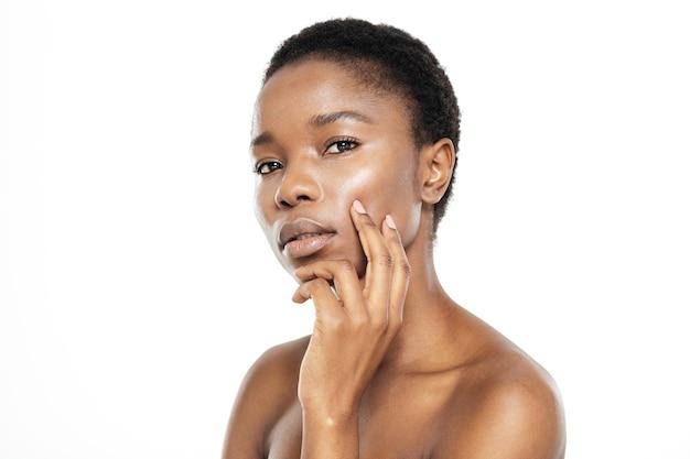 Piękno portret uroczej afroamerykańskiej kobiety ze świeżą skórą, patrząc na kamerę na białym tle