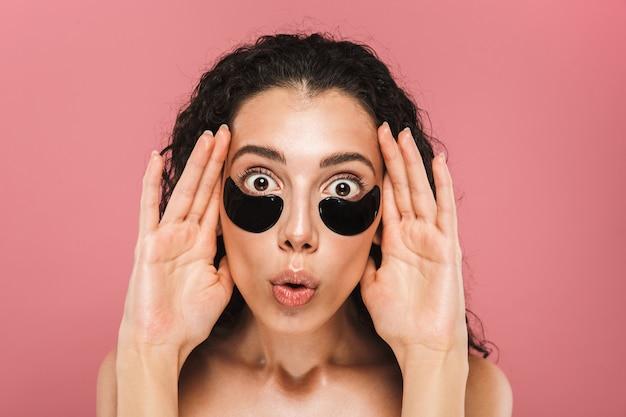 Piękno portret uroczej kobiety bez koszuli z długimi włosami brunetki noszącej kosmetyczne plastry pod oczami, odizolowane na różowej ścianie