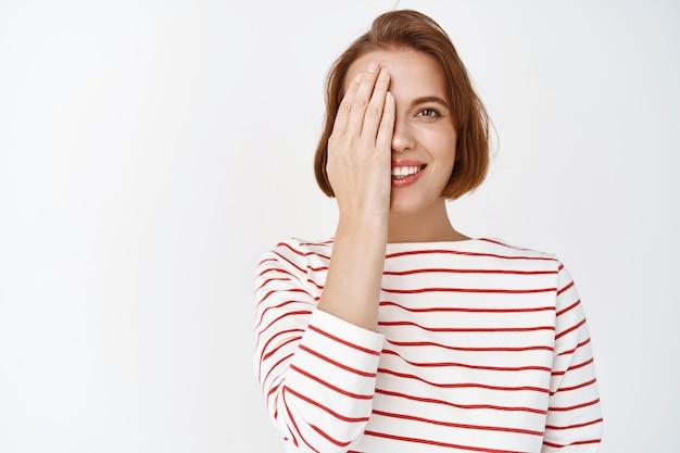 Piękno. portret uroczej uśmiechniętej kobiety zakrywającej pół twarzy dłonią i wyglądającej na szczęśliwą, pokazującą przed efektem pielęgnacji skóry po kosmetykach, stojącą na białej ścianie