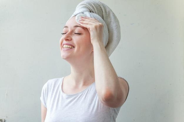 Piękno portret uśmiechnięta kobieta w ręcznik na głowie z miękką zdrową skórę usuwania makijażu z wacikiem na białym tle.