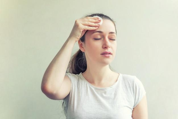 Piękno portret uśmiechnięta kobieta z miękkiej zdrowej skóry usuwanie makijażu z wacikiem na białym tle. pielęgnacja skóry oczyszczająca koncepcja relaksu spa