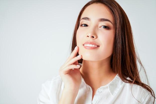 Piękno portret uśmiechnięta zmysłowa azjatykcia młoda kobieta z czystą świeżą skórą w białej koszula