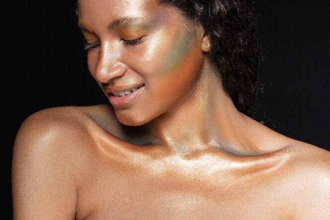Piękno portret uśmiechniętej amerykańskiej młodej kobiety ze stylowym makijażem na czarno
