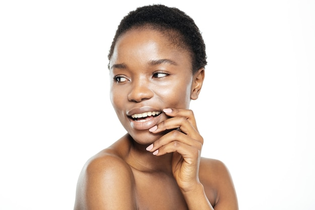Piękno portret uśmiechniętej kobiety ze świeżą skórą odwracającą wzrok na białym tle