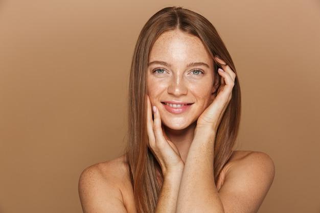 Piękno portret uśmiechniętej młodej kobiety topless z długimi rudymi włosami pozowanie, trzymając się za ręce na jej twarzy odizolowanej na beżowej ścianie