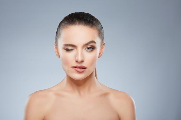Piękno portret uwodzicielskiej dziewczyny patrząc na kamery. głowa i ramiona pięknej kobiety przygryzającej dolną wargę i mrugającej okiem. naturalny makijaż, studio, prawdziwe emocje