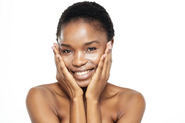 Piękno portret wesołej afroamerykańskiej kobiety patrzącej na kamerę na białym tle