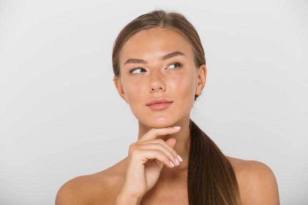 Piękno portret zadowolonej kobiety bez koszuli z długimi brązowymi włosami, patrząc na bok, na białym tle