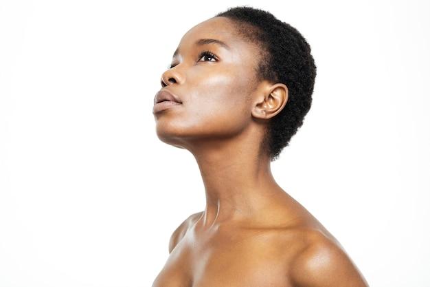 Piękno portret zamyślonej afroamerykańskiej kobiety patrzącej w górę na białym tle na białym tle
