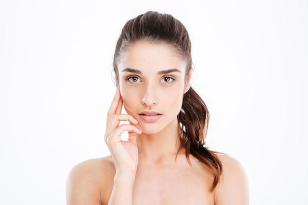Piękno portret zmysłowej młodej kobiety dotykającej skóry na twarzy nad białą ścianą