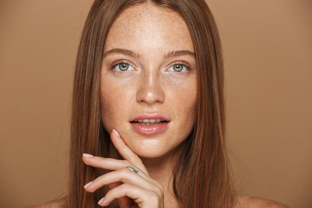 Piękno portret zmysłowej młodej kobiety topless z długimi rudymi włosami pozowanie, trzymając się za ręce na twarzy odizolowanej na beżowej ścianie