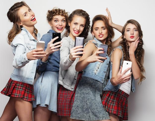 Piękno, przyjaźń, młodość i technologia. studio portret pięciu wspaniałych młodych kobiet przy selfie.