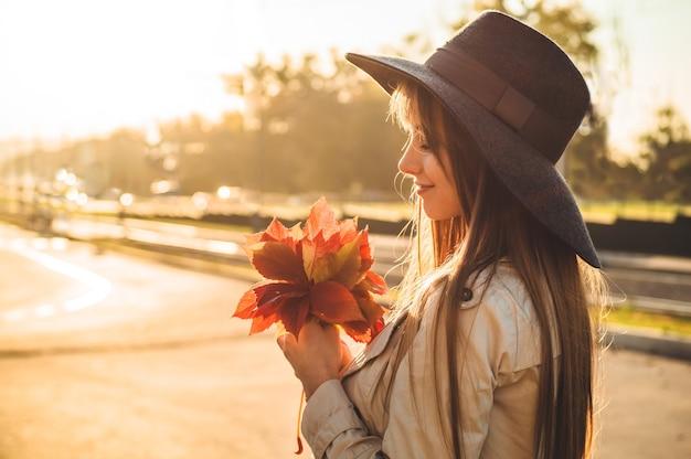 Piękno romantyczna kobieta na zewnątrz korzystających z natury, trzymając w rękach liście. piękny model jesień z falującymi blaskami włosów. światło słoneczne na zachodzie słońca. portret romantycznej kobiety