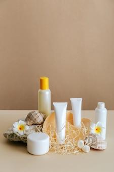 Piękno skład produktu kosmetycznego do pielęgnacji skóry z muszli na beżowym tle kamiennym cokole. naturalna kremowa butelka kosmetyczna tuba makieta z tropikalnymi kwiatami.