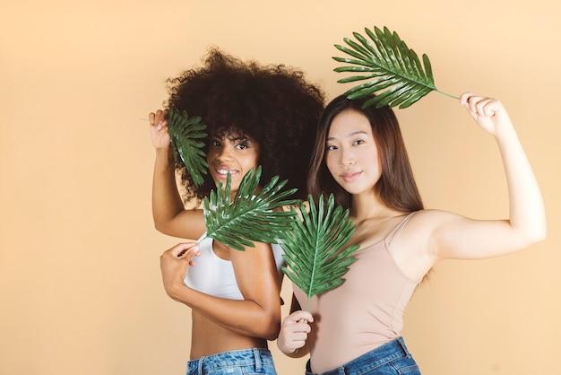 Piękno. uśmiechnięte kobiety o idealnej skórze i naturalnym makijażu portrety, azjatki i afrykanki, trzymające liście palmowe