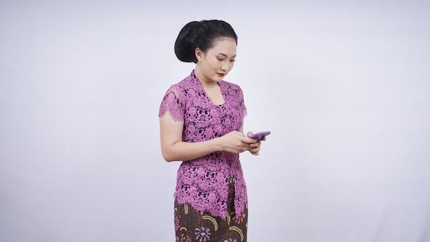 Piękno w kebaya bawiące się telefonem komórkowym na białym tle