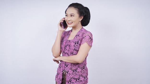 Piękno w kebayowej zabawie przez telefon na białym tle