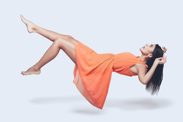 Piękno w powietrzu. pełnej długości studio strzał atrakcyjnej młodej kobiety w pomarańczowej sukience, unoszącej się w powietrzu i patrzącej na zaskoczoną