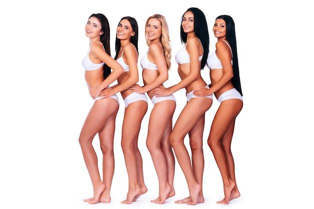 Piękno w rzędzie. widok z boku na całej długości pięciu pięknych kobiet w bieliźnie patrzących na kamerę i uśmiechających się, stojąc na białym tle