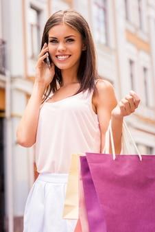 Piękno w telefonie. piękna młoda uśmiechnięta kobieta trzymająca torby na zakupy i rozmawiająca przez telefon komórkowy, stojąc na zewnątrz