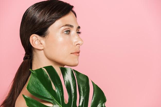 Piękno widok z boku portret atrakcyjnej zdrowej topless brunetki na białym tle, pokrywa z tropikalnym liściem