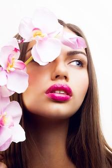 Piękno wiosenny portret delikatnej uwodzicielskiej damy z różowymi kwiatami, dużymi ustami i naturalnym makijażem